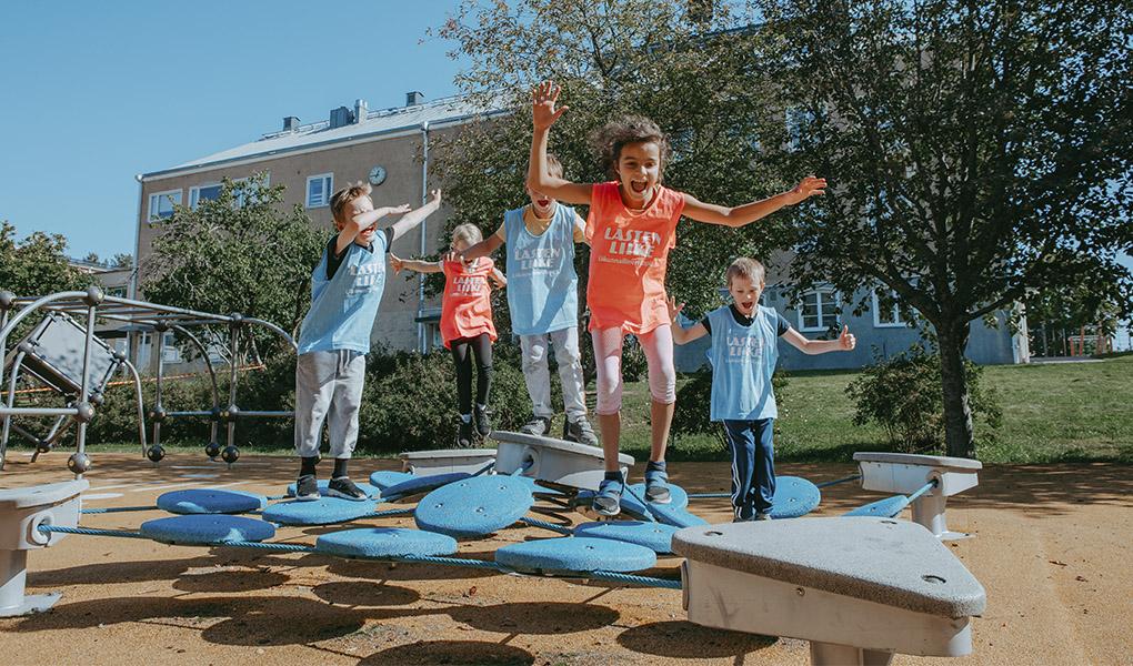 Kuvassa lapset hyppelevät koulunpihan telineissä