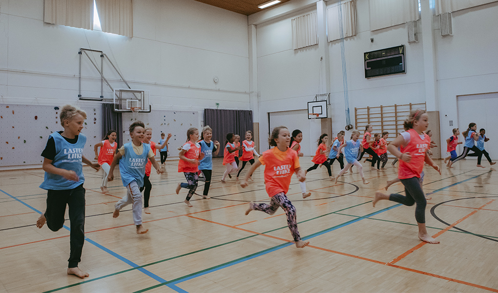 Kuvassa lapset juoksevat koulun liikuntasalissa