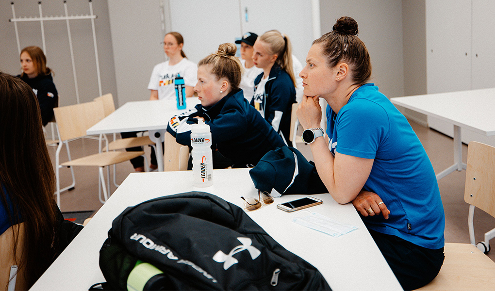 Kapteeni Jenni Hiirikoski kuuntelee asiantuntijanäkemystä urheilijan terveyttä edistävistä toimintamalleista. Kuva: Jesse Väänänen